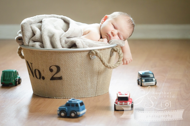 Baby Bryce - sleeping in a bucket surrounded by toy cars
